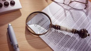 Contract with magnifying glass showing a contract for renting out property