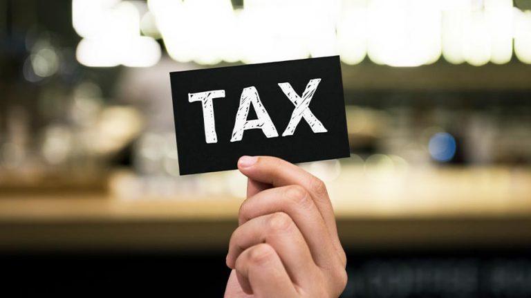 Vastgoed exploitatie of belegging - hand houdt bordje met tax omhoog